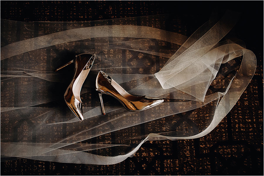 bride's gold heels lay over veil in fairmont banff springs