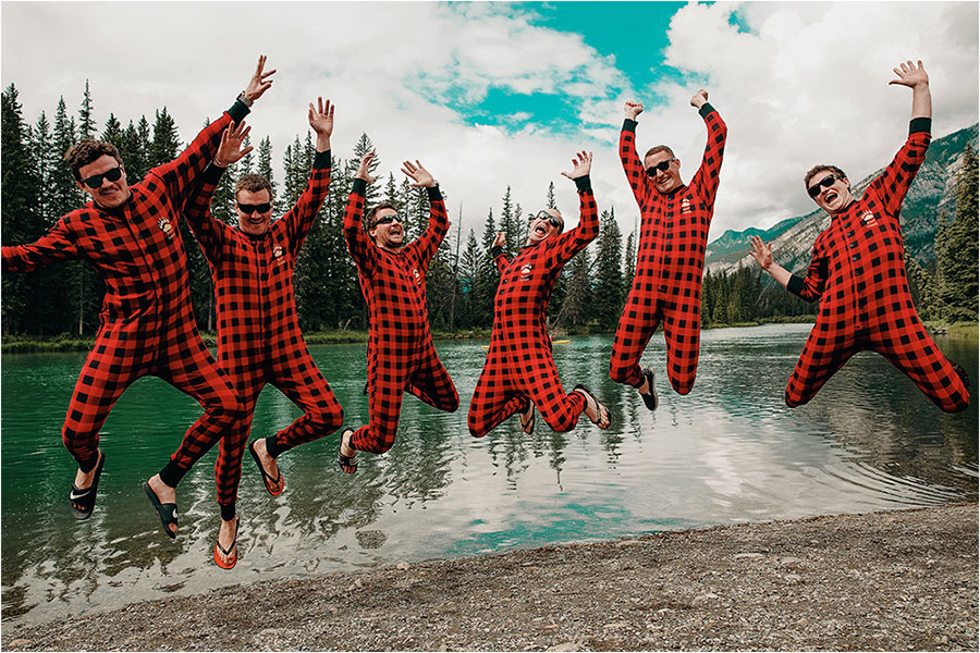 groomsmen in plaid onesies jump in air with excitement