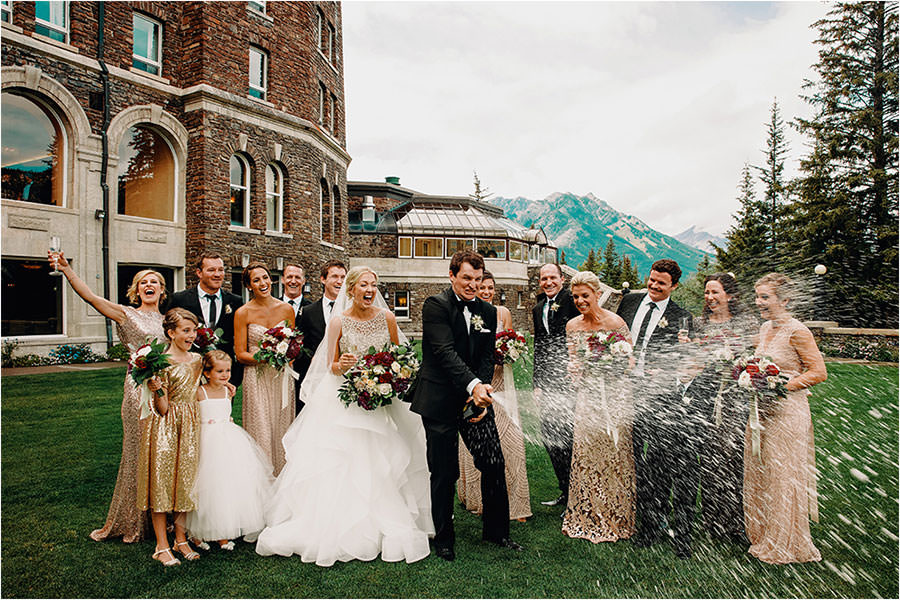 bridal party cracks open champagne bottle just outside of the fairmont banff springs