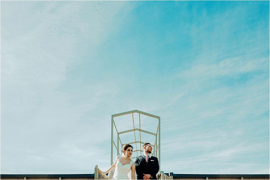 bride and groom against blue sky in sudbury