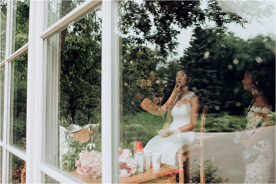 bride looks through window while getting makeup done at king valley golf club