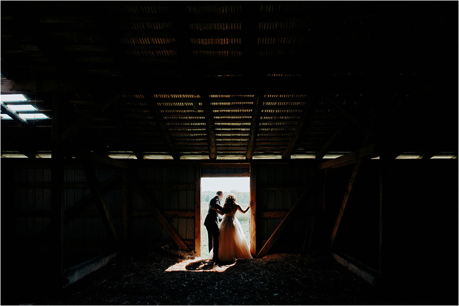 bride and groom look out doorway of barn on manitoulin island
