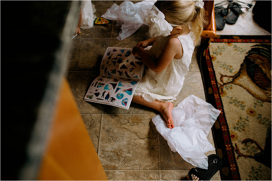 flower girl plays with sticker book before wedding