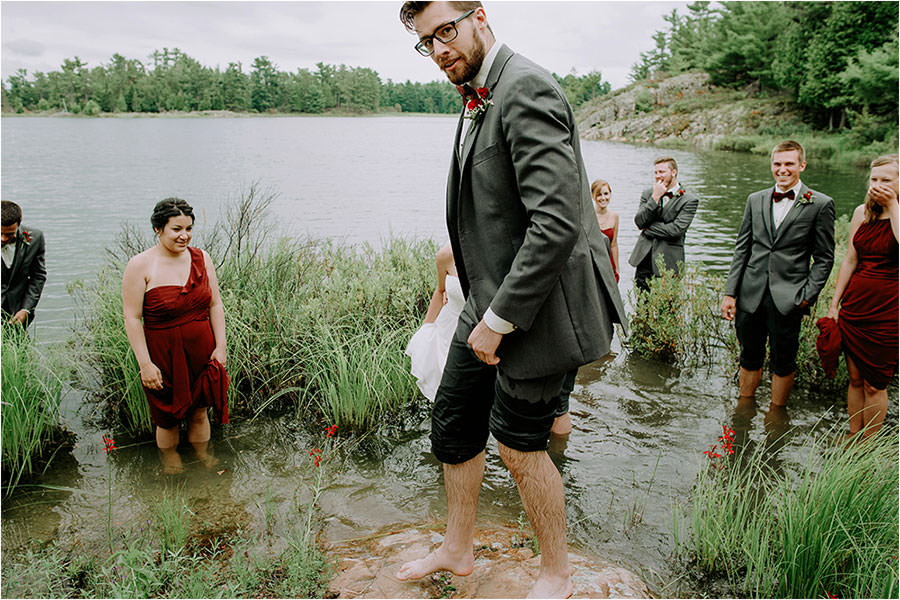 groomsman eyes camera with wet rolled up pants