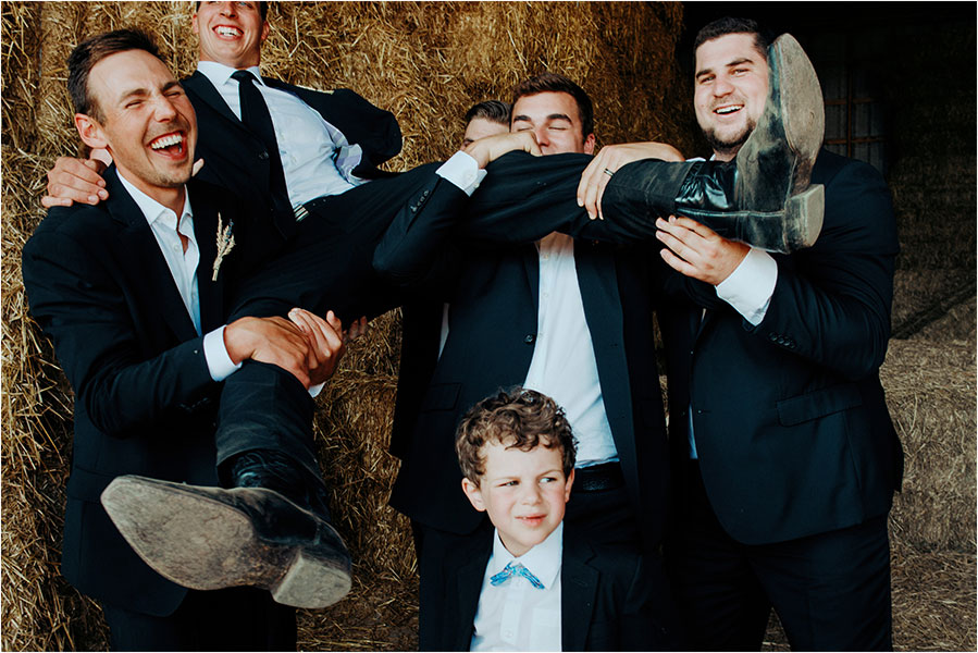 groomsmen laugh while holding up groom