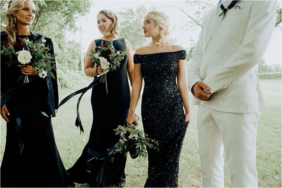 bridesmaids wait for ceremony in black dresses with bouquets
