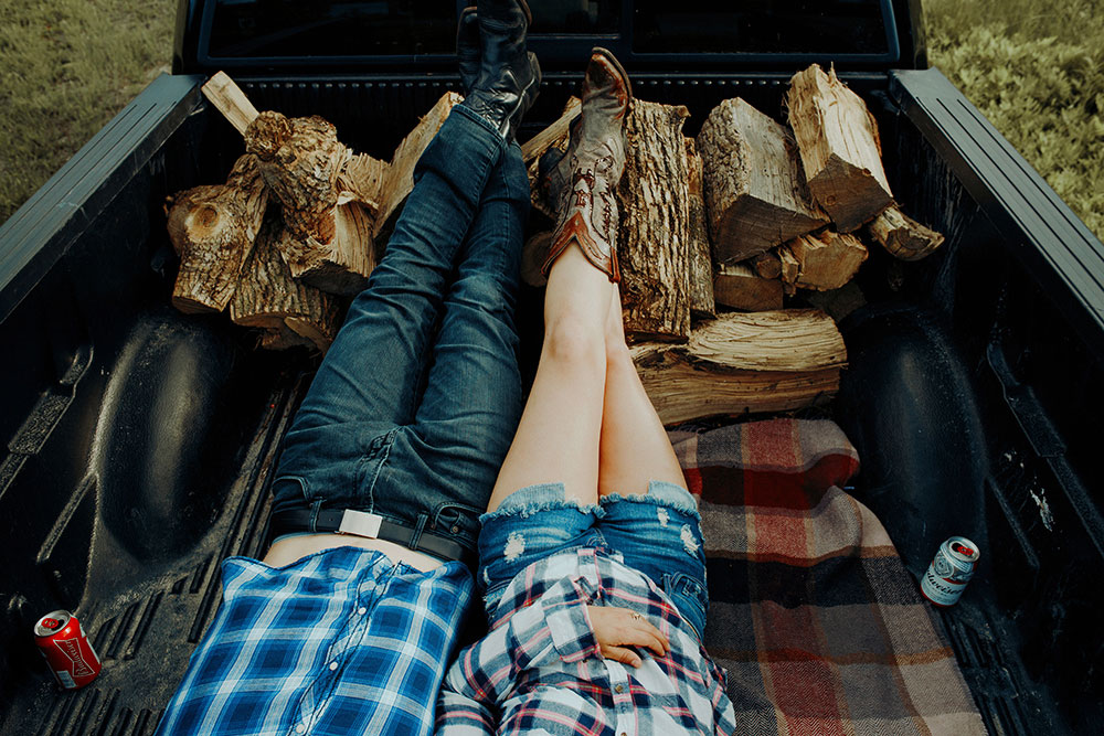couple in plaid and jeans lay cozy in back of truck