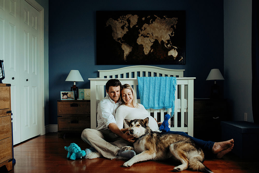 sudbury couple sit laughing in nursery with dog
