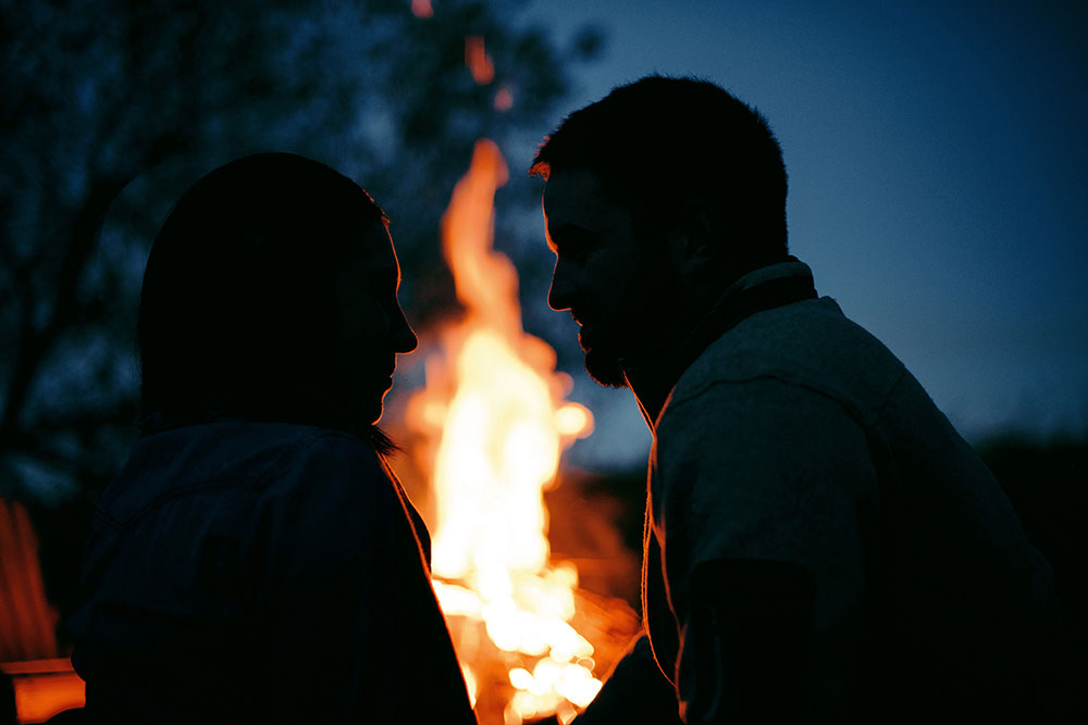 couple enjoy fall night by the bon fire