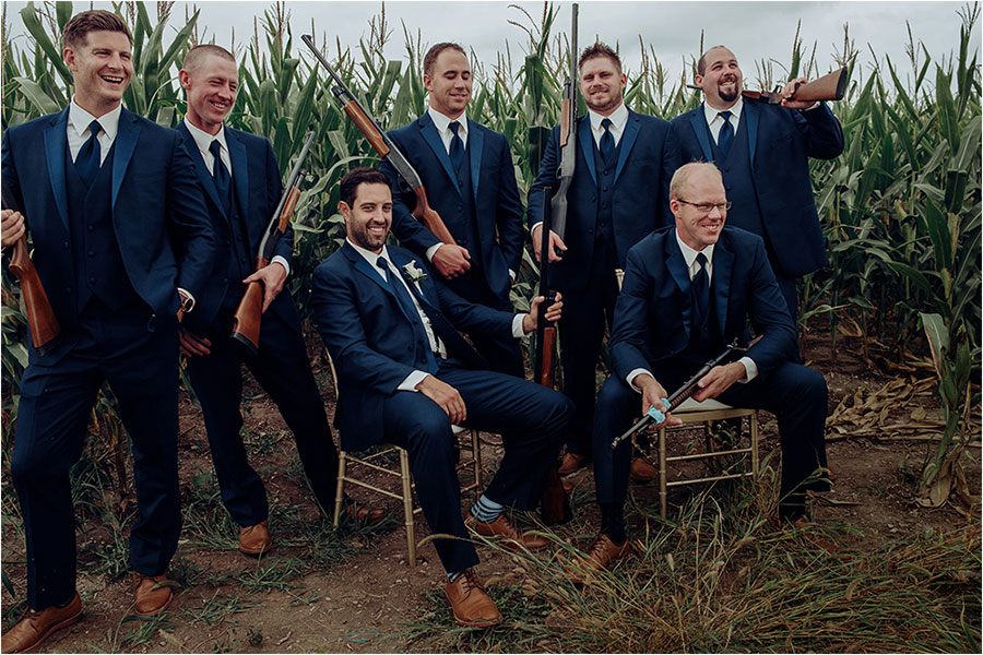 groomsmen in blue suits hold rifles in exeter cornfield