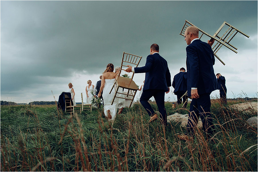 bridal party walks away carrying gold chairs under exeter dark clouds