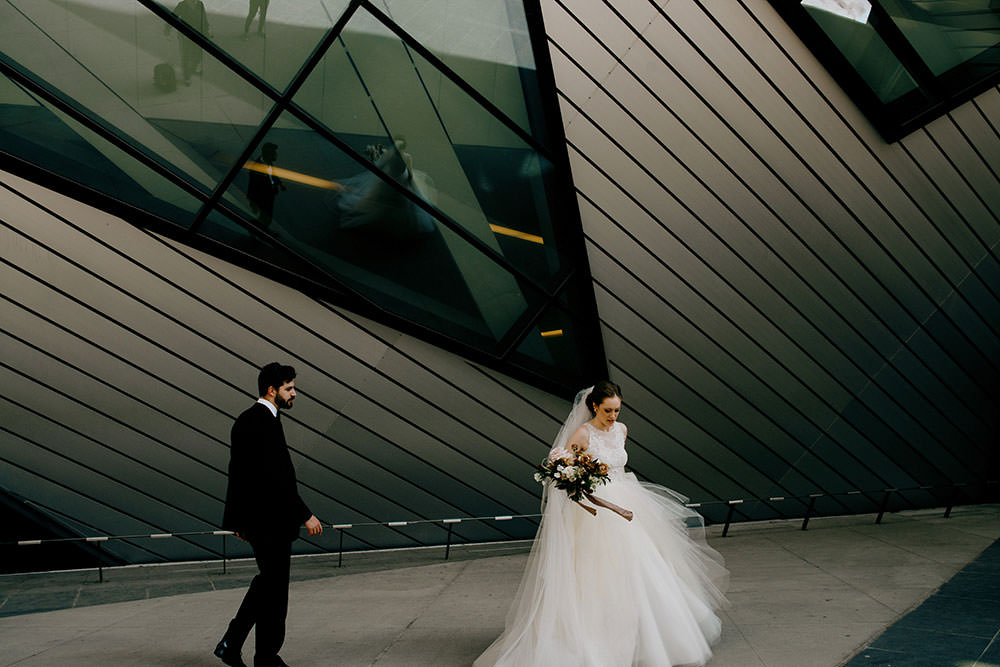 bride and groom stand in front of toronto ROM