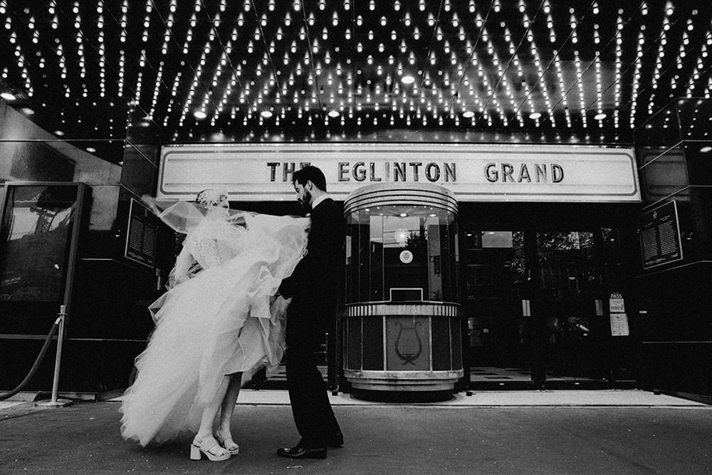 bride and groom pose in front of eglinton grand toronto