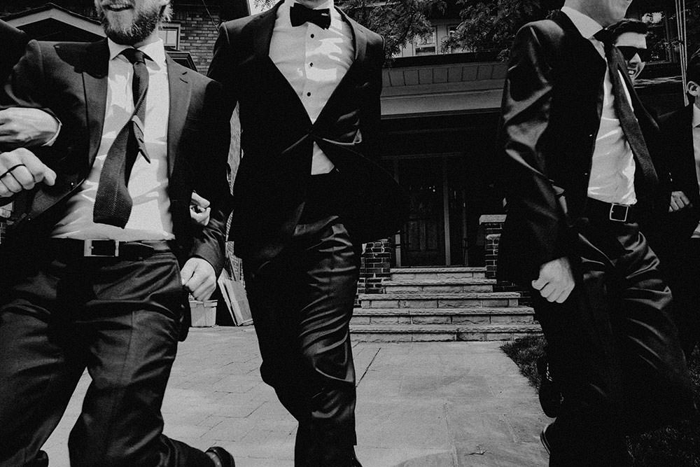 dapper groomsmen run past camera