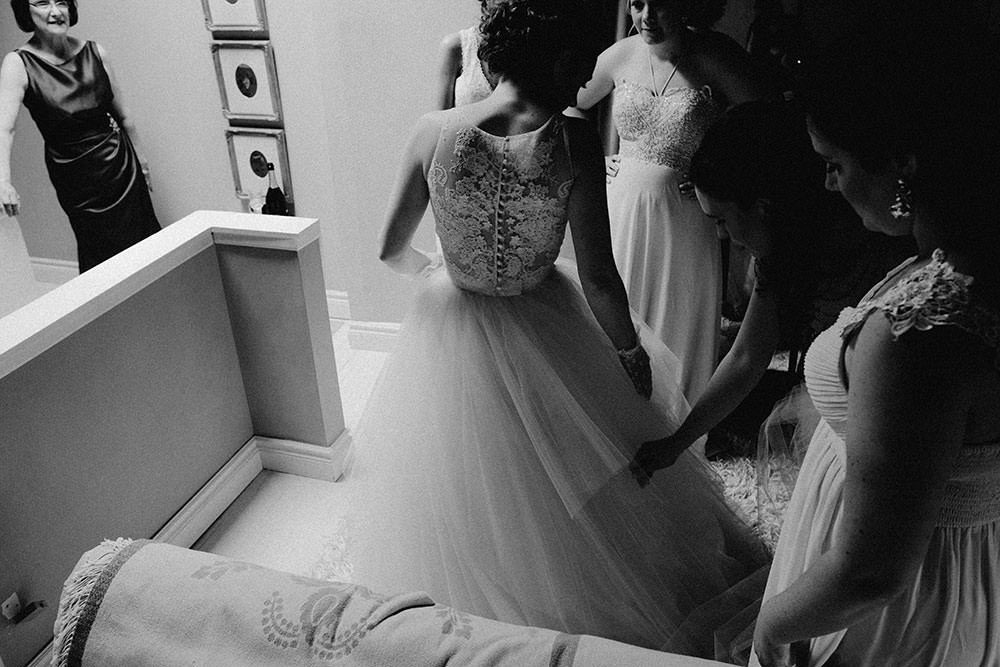 bridesmaids help bride put on gown