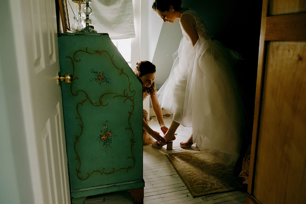 bridesmaid helps bride put on shoe