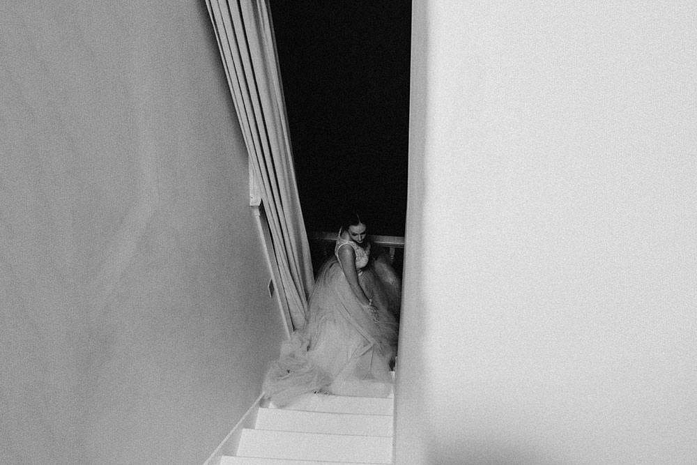 bride looks back at bottom of staircase