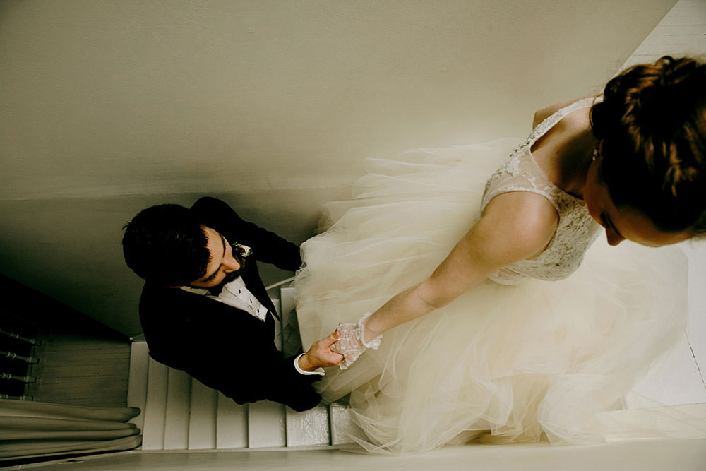 bride guides groom upstairs by hand