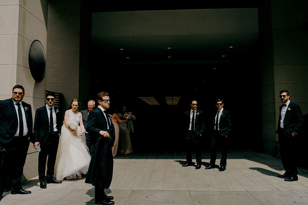 bridal party walks together between buildings downtown Toronto