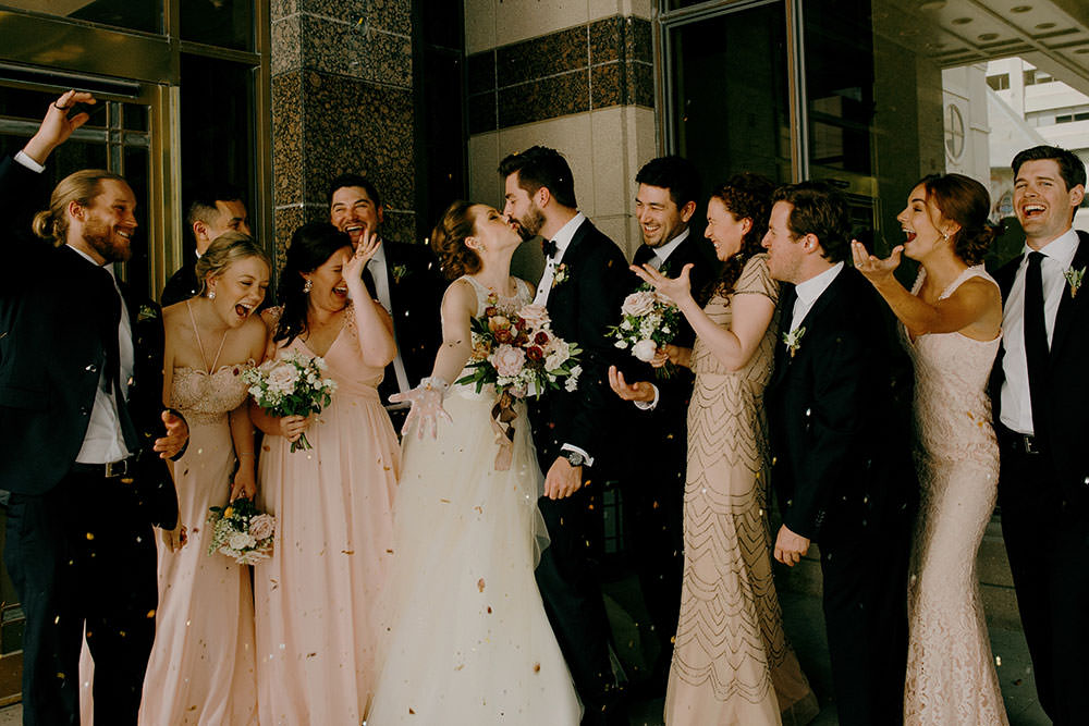 bridal party celebrate while bride and groom kiss