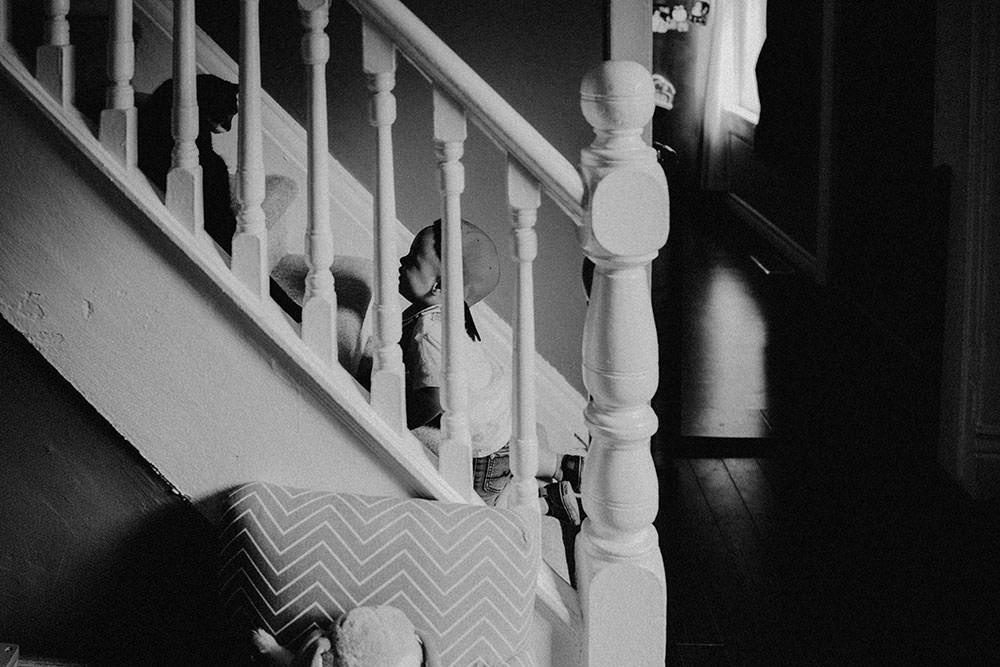 sudbury family portrait boy looks at cat on staircase