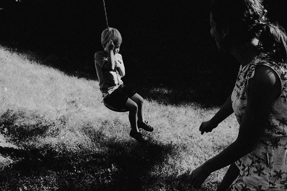 kids plays on swing in family portrait