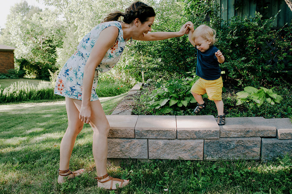 mom helps son walk in family portrait