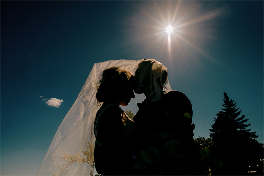 bride and groom in silhouette at ramsey lake in sudbury