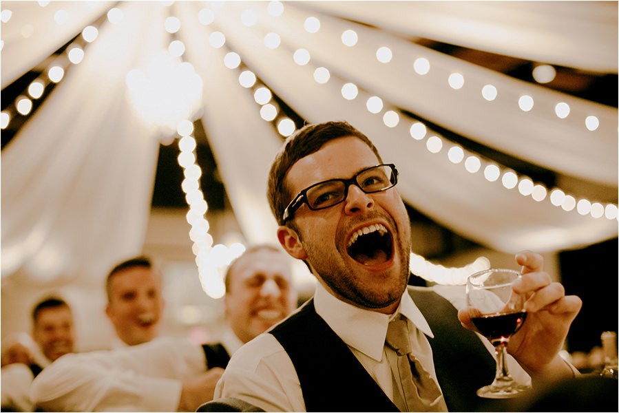 groomsman laughs at speeches during sudbury wedding at the caruso club