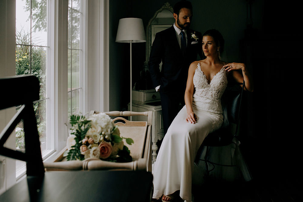 Bride and groom pose in window light at the Belcroft estates