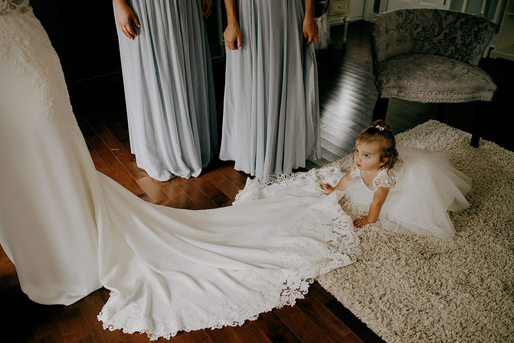 flower girl plays with dress at the Belcroft Estates