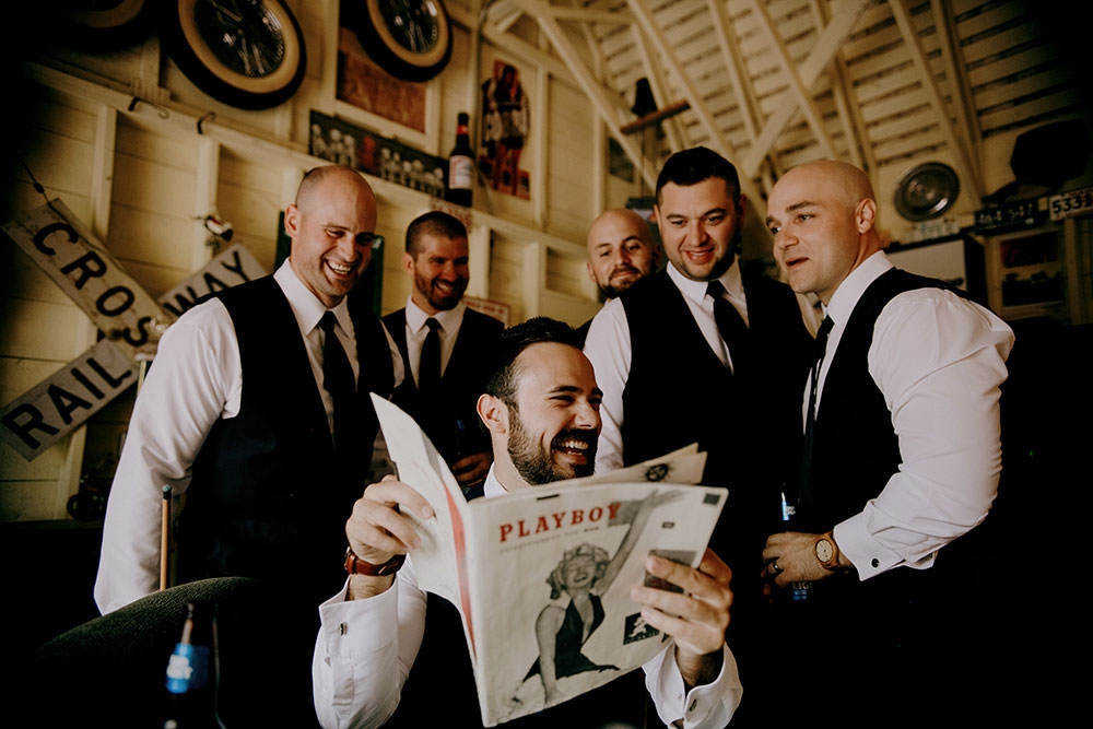 Groomsmen enjoy vintage playboy magazine at Belcroft estates