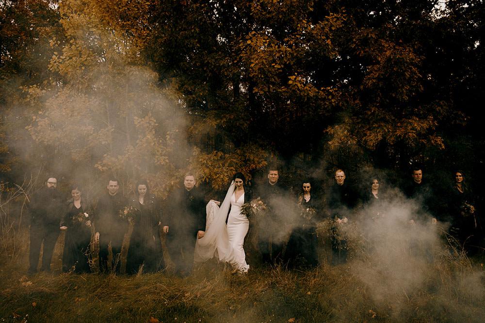 Bridal Party walk through a cloud of smoke in feild