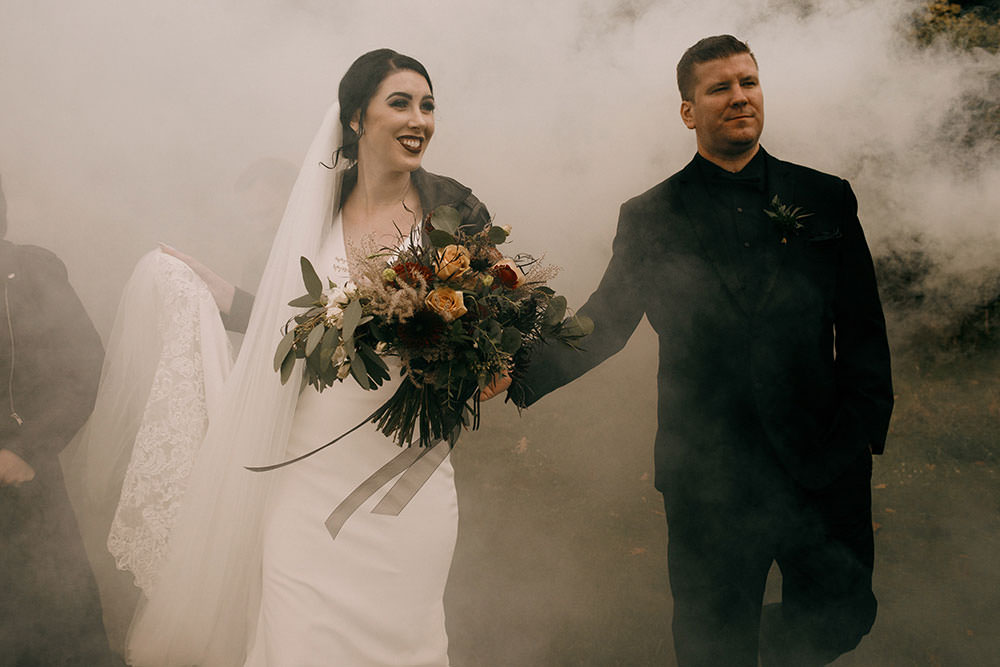 Bride and groom walk through a could of smoke