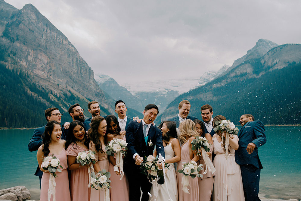 Bridal party pop champagne bottle at the Fairmont Chateau Lake Louise