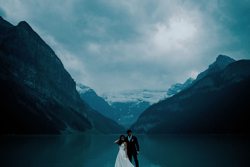 Bride & groom stand in front of the Fairmont Chateau Lake Louise
