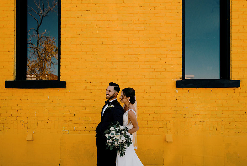 wedding couple poses in front of yellow wall in Sudbury