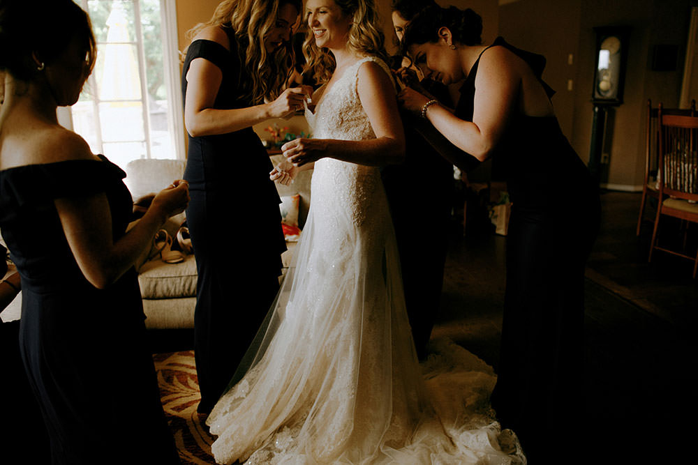 bridesmaids help bride get gown on at idylwylde wedding