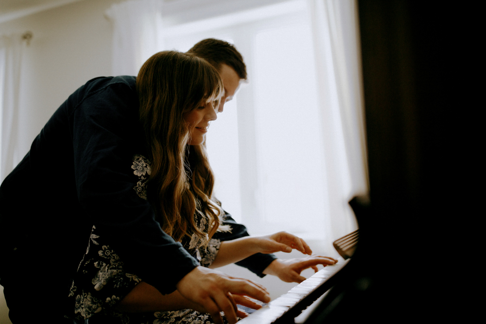 couple plays piano in engagement photography session in their innisfil home