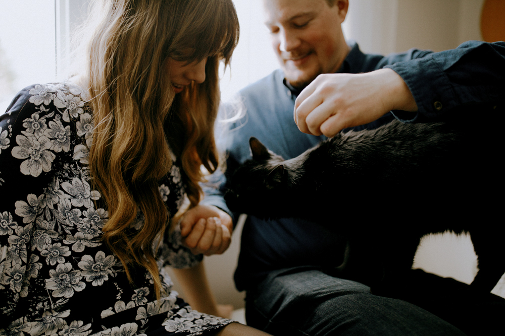 couple plays with cat in engagement photography session in their innisfil home