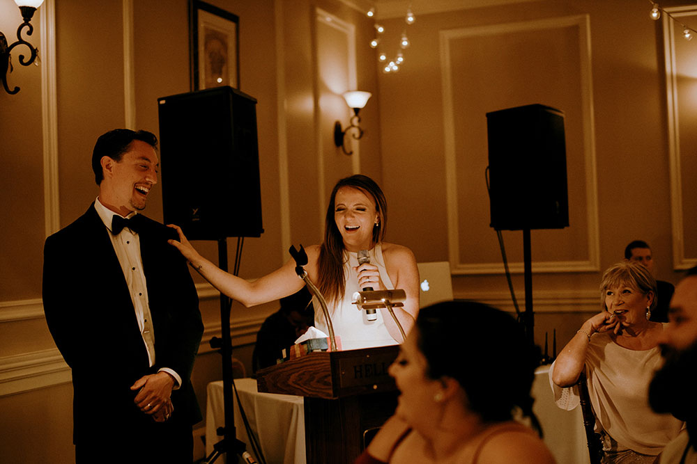 bride and groom laugh at speeches at the hellenic centre in sudbury