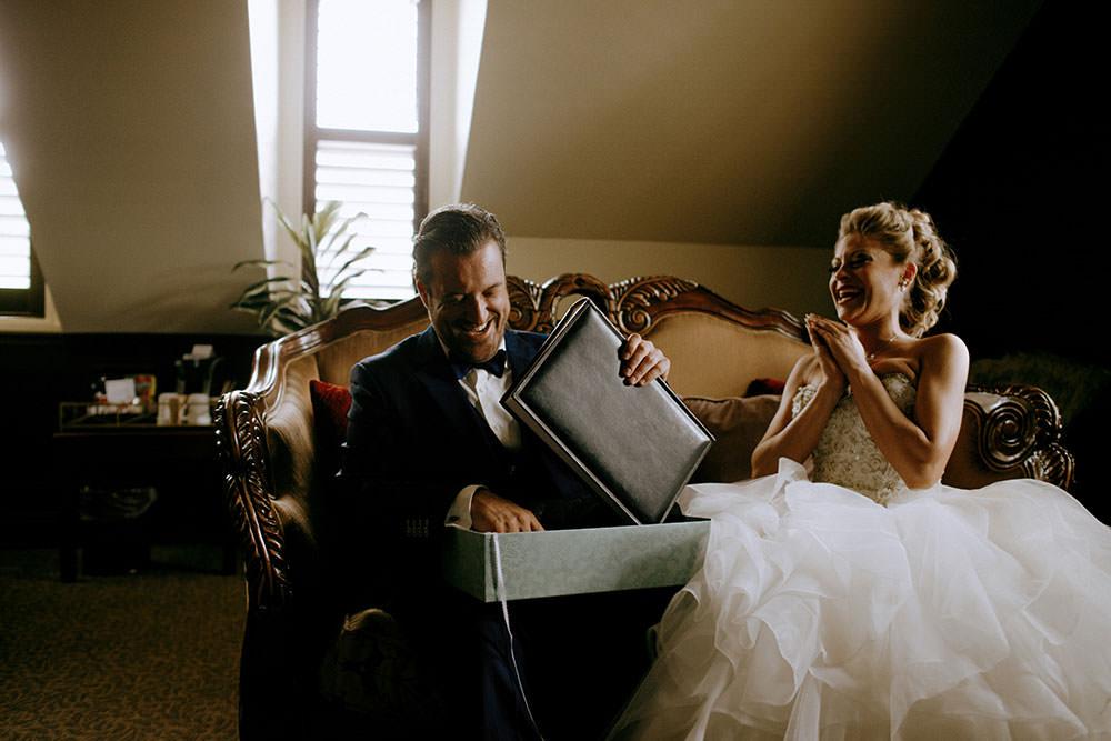 Paris Ontario Wedding groom opens gift from bride