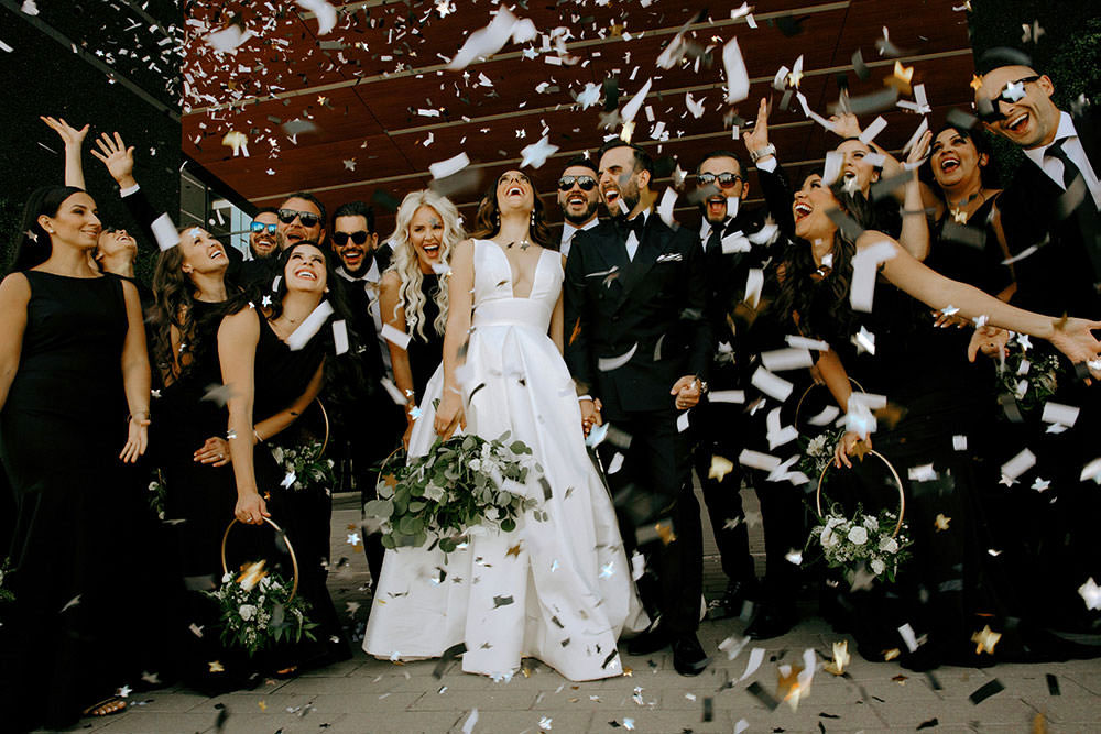 award winning wedding photography in ontario where bridal party celebrates with confetti