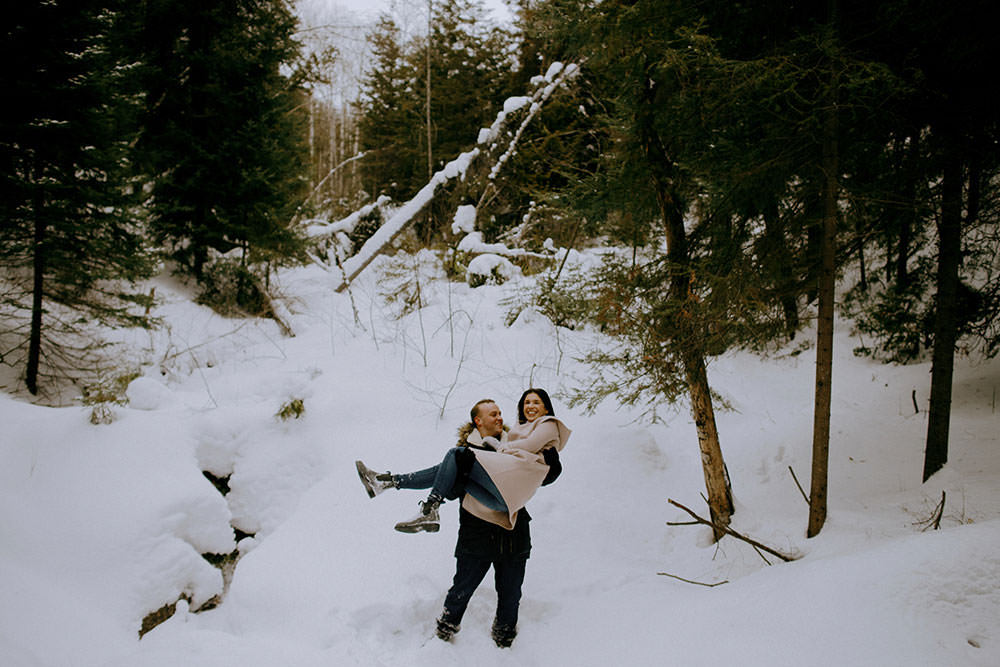 couple plays in snow on trail in ontario engagement session