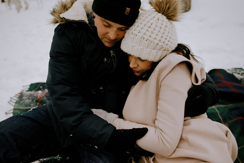 couple has fun on winter hiking trail in ontario engagement session