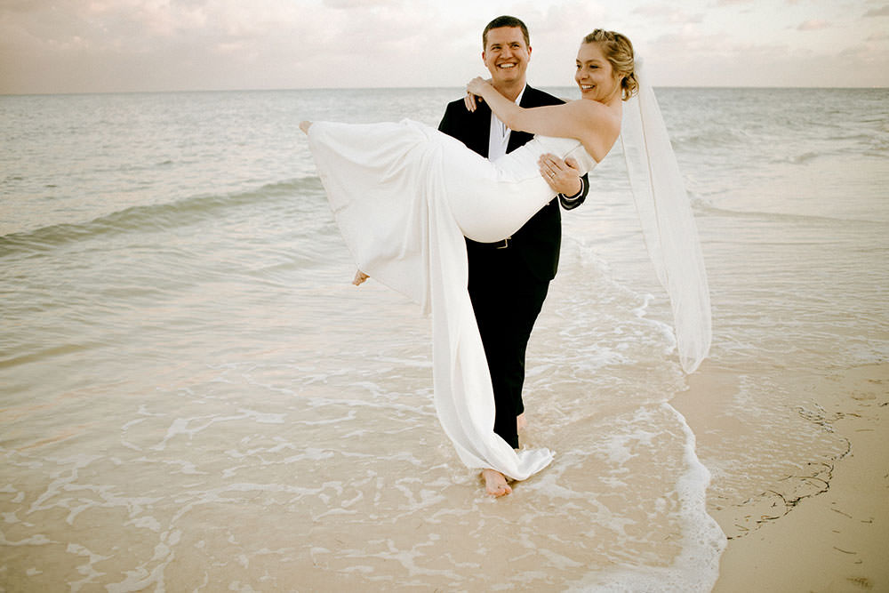 Royalton Riviera Cancun Wedding groom carries bride down beach
