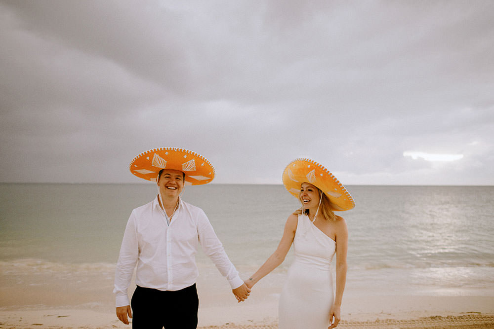 Royalton Riviera Cancun Wedding couple laugh wearing sombraros