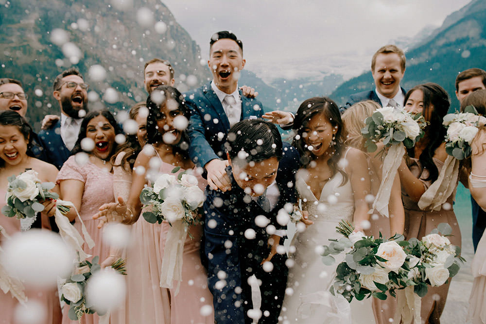 fairmont lake louise bridal party portrait of them popping champagne bottle in celebration