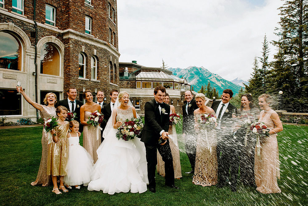 fairmont banff springs bridal party portrait of them popping champagne bottle in celebration