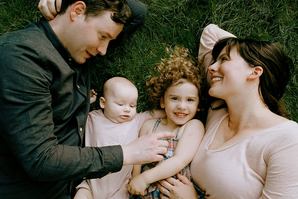 sudbury family portrait with family cuddled in back yard